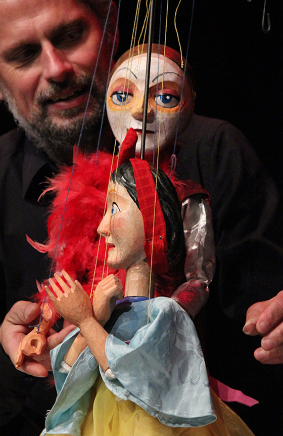 Puppeteer manipulating two wooden puppets.
