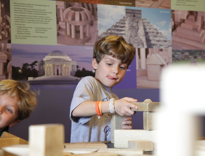 A boy creating a structure using wooden blocks.