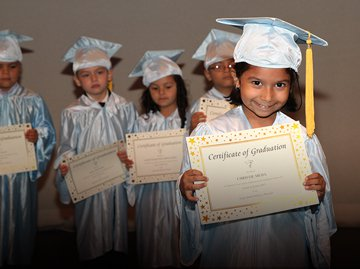 Pre-K students dressed in their graduation cap and gown holding diplomas.