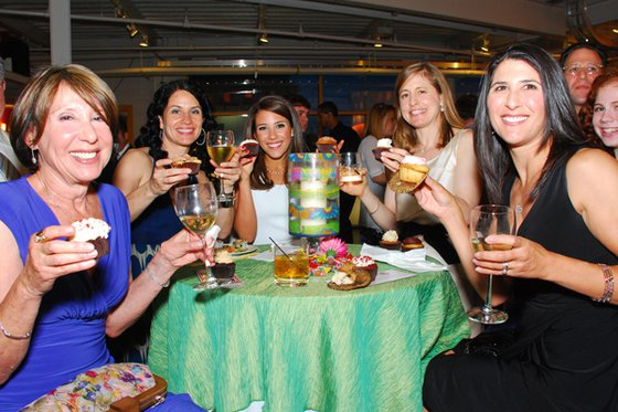 A group of women sitting together at a decorated table holding drinks.