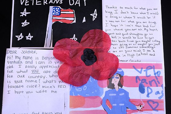 large red poppy placed on postcards with written messages and drawings by kids to veterans
