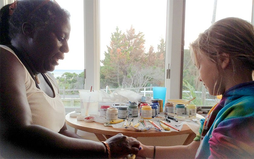 Artist Kooy sitting and speaking with young artist painting her hand.