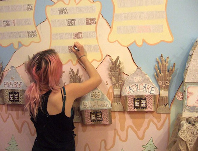 An artist creating a mural which includes store fronts using a marker.