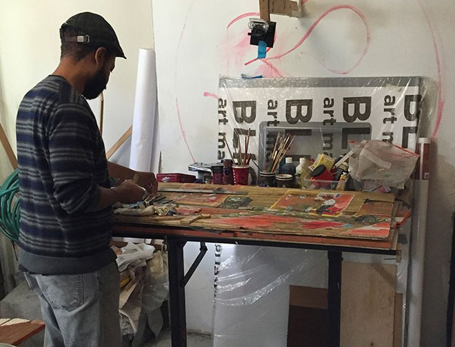 Artist Javaka Steptoe creating artwork at his worktable.