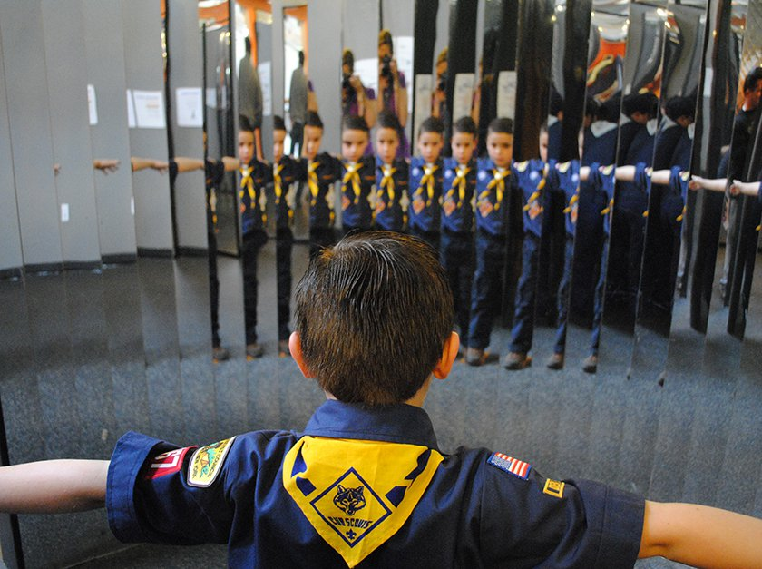 A Boyscout standing in front of the mirror looking at his many reflections.