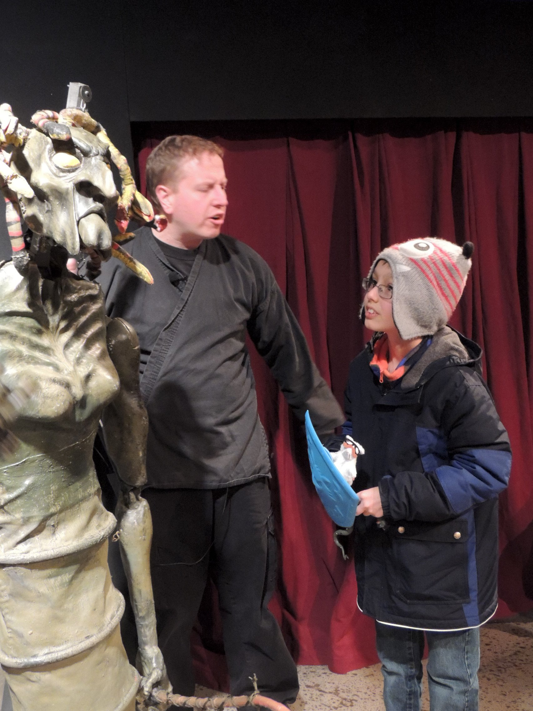 A large puppet on stage with its puppeteer and a member of the audience.