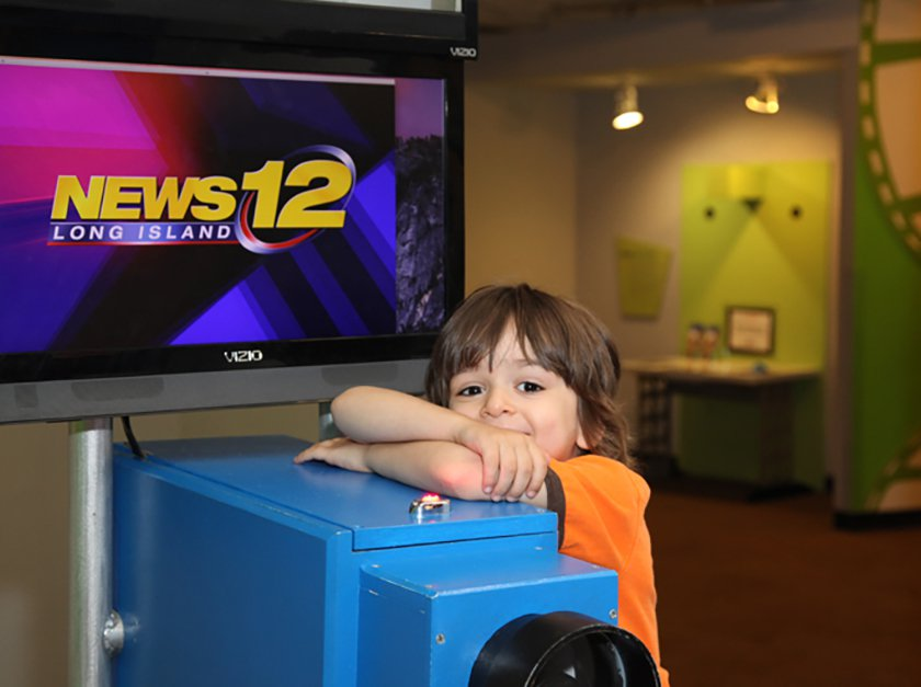 A child leaning on the News12 wooden Camera.