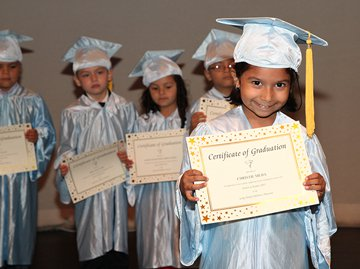 Pre-K students dressed in their graduation cap and gown holding diplomas