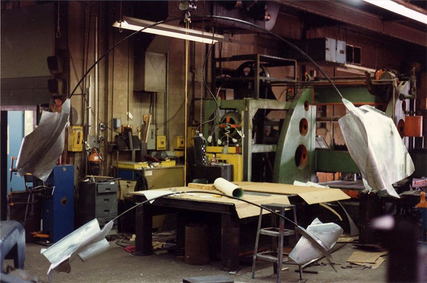 A metal sculpture being created in a workshop. The sculpture has two large pieces at each end, and a thin, bent piece of metal connecting the two.