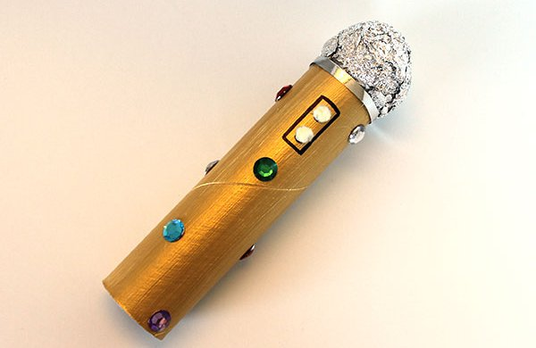 A golden microphone made with a toilet paper roll, tin foil and plastic gems.