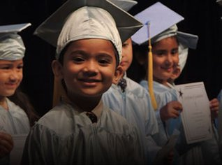Pre-K program graduate in cap and gown on stage.
