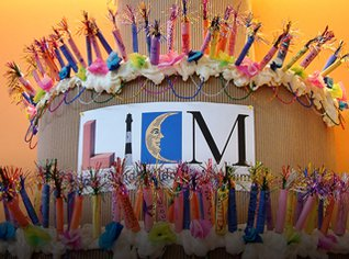 Giant cardboard birthday cake with paper candles and LICM logo.