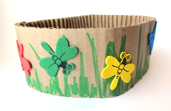 A cardboard crown crafted with butterfly stickers and green grass.