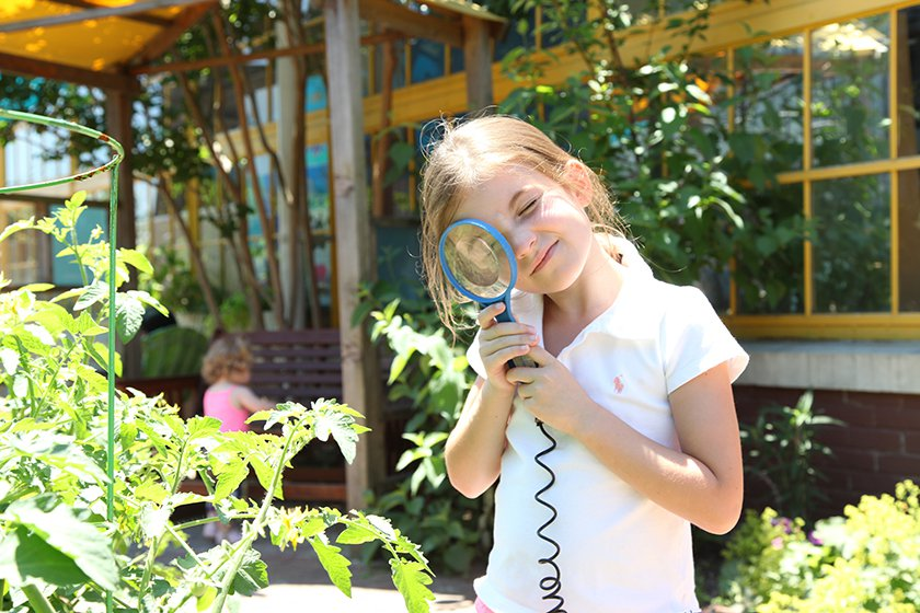 A girl using a magnifying glass to look at a plant in Museum's garden.