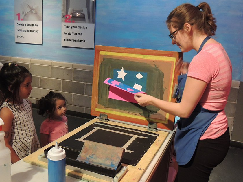 An educator showing two young visitors how to create screen-printed work.