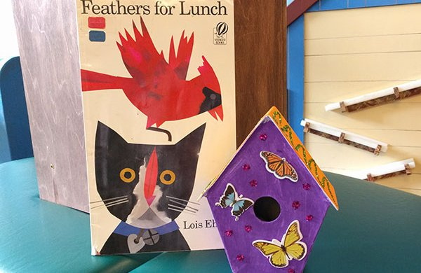 "The book ""Feathers for Lunch"" next to a hand-made colored wooden bird house."