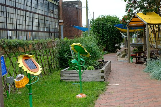 Our Backyard exhibit at LICM featuring two large metal sunflowers, a planter box and a brick pathway.