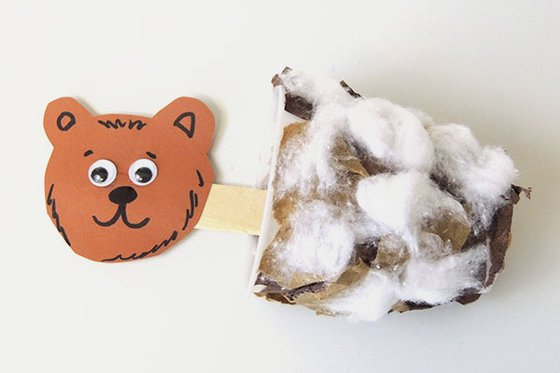 A paper brown bear face attached to a cottonball body with a popsicle stick.