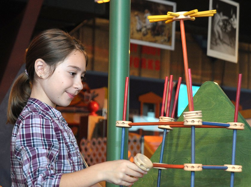 girl building with giant Tinkertoy pieces