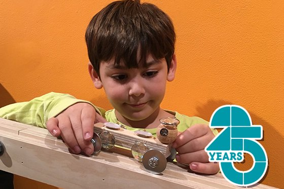 A child holding a model car on a ramp with the LICM 25th birthday logo in the right corner.