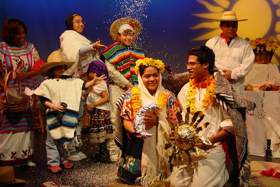 A group of adults and children wearing native Mexican wedding attire.