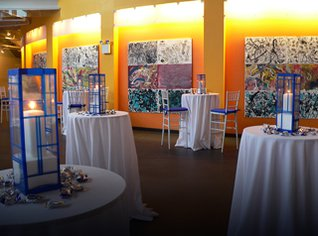 Tables decorated with blue candles and tableclothes in outter lobby of Museum.