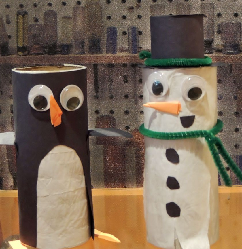 Two toilet paper rolls made into a snowman and penguin using construction paper.