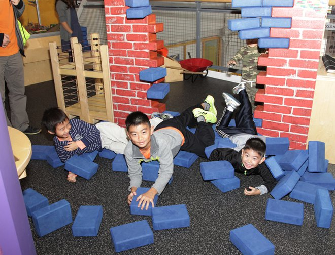 Boys laying on the floor after knocking over their brick wall creation.