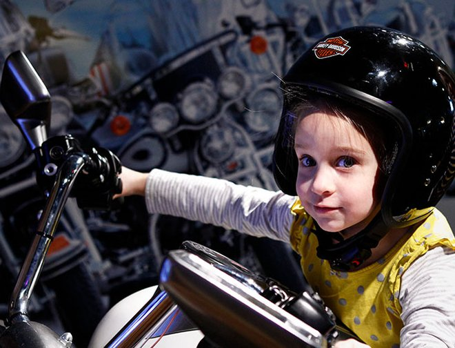 Child sitting on motorcycle wearing a helmet in exhibit.
