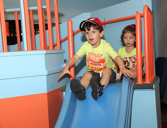 Boy and girl getting ready to slide down lighthouse slide