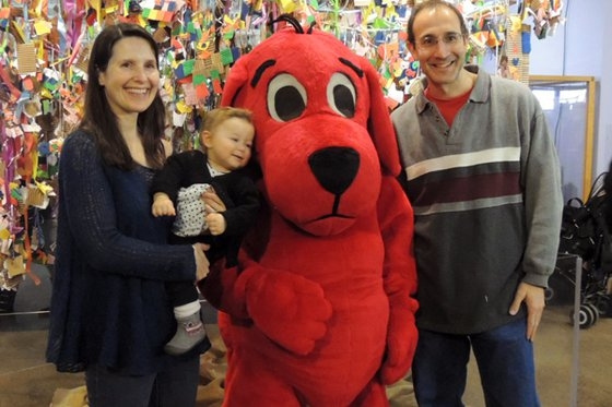 Family standing next to Clifford the Big Red Dog.