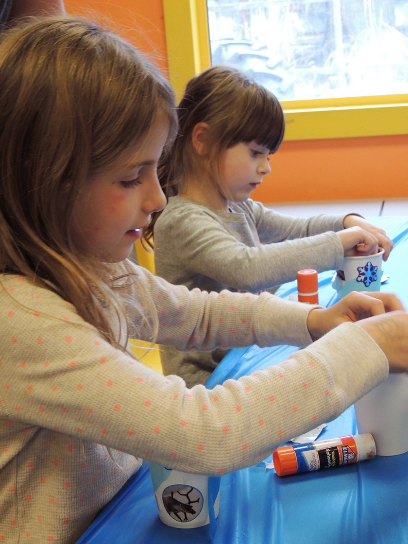 Two girls decorating cups for their experiment.