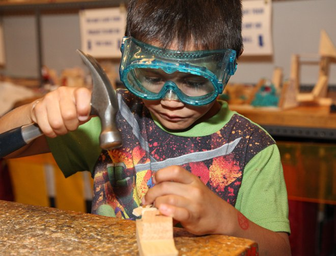 Boy using a hammer and nail to create wooden project while wearing safety googles.