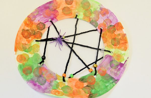 A paper plate decorated with pink, orange and green paint made with black yarn to mimic a spiderweb and a small plastic spider.