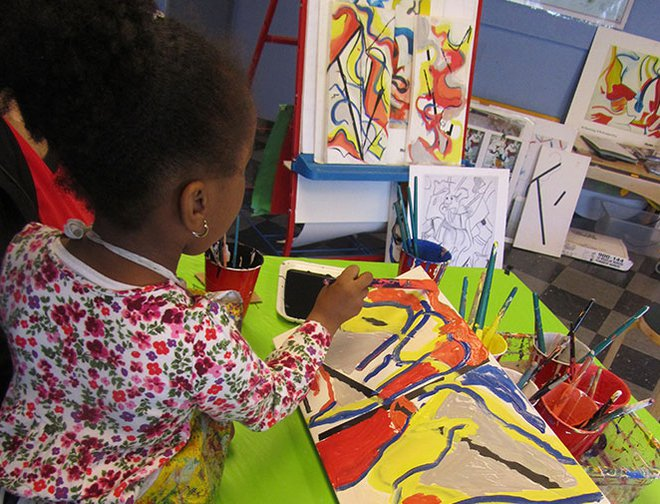 A young artist painting her DeKooning inspired piece on canvas.