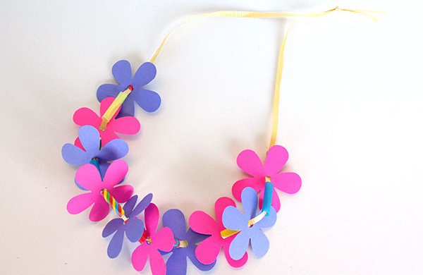 A necklace constructed with paper colorful flowers, beads and ribbon.