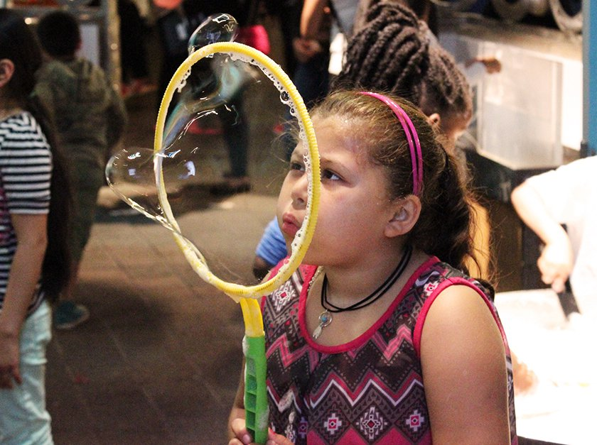 A girl blowing a bubble with a bubble wand.