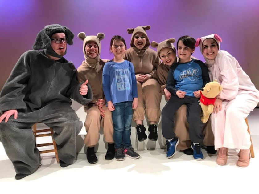 Five actors in costume pose with two members of the audience on LICM stage.