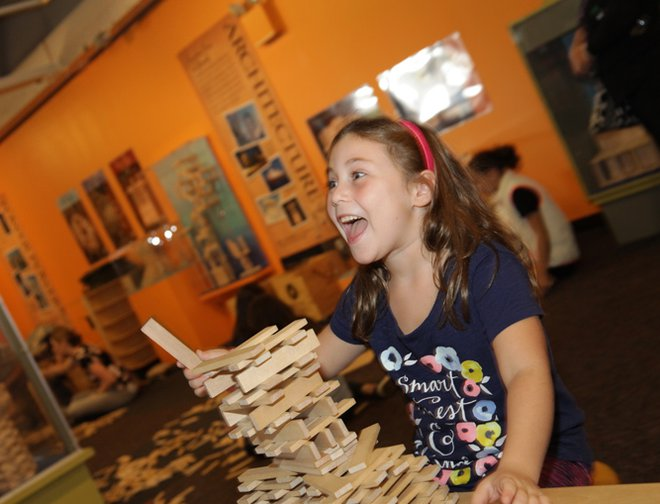 A girl playing with KEVA blanks and building a structure.