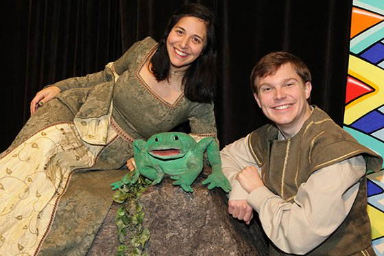 Two cast members on stage with frog puppet.