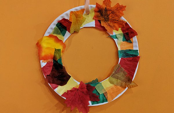 "Circular wreath made from paper plate covered with red, yellow, brown and green tissue paper ""leaves."""