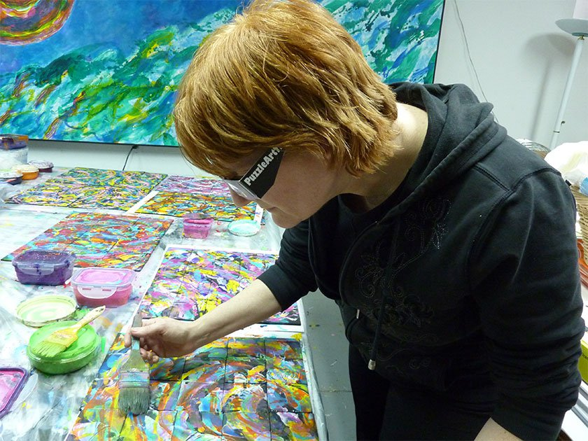 An artist painting on small piece of square canvas with varying colors.