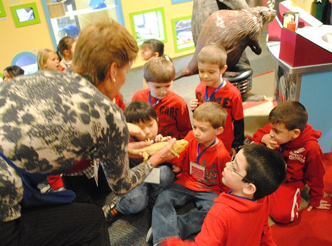 LICM educator showing a group of children a live bearded dragon.