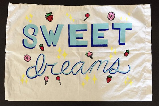 "A white pillow case decorated with cursive text reading ""sweet dreams"" and ice-cream, strawberries, donuts and lollipops."
