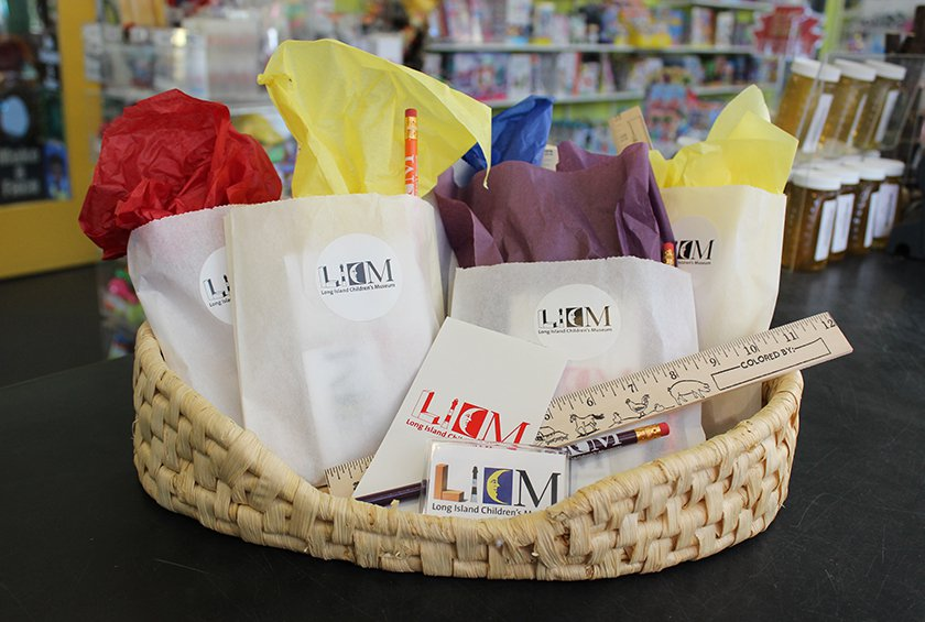 White LICM gift bags filled with colored tissue paper in a basket.