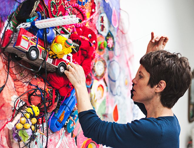 Artist with sewing needle adding brightly colored fabric and discarded toys to a canvas.