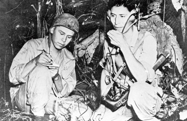 Two Navaho soldiers relay orders over a field radio in their native tongue during World War 2.