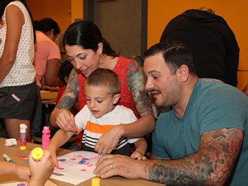 A family working together to complete a craft in the museum studio.