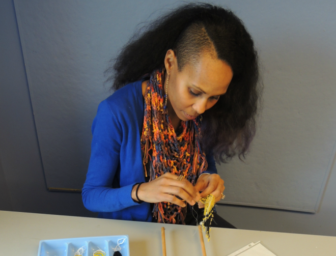 Artist creating a beaded necklace with yellow and black beads using a beading loom.