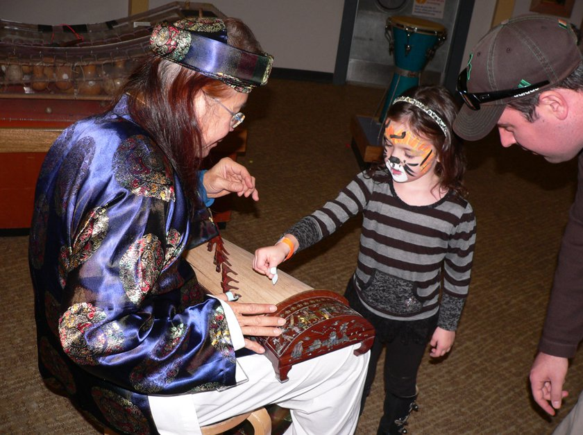 Child learning about Tet cultural from adult dressed in traditional attire.